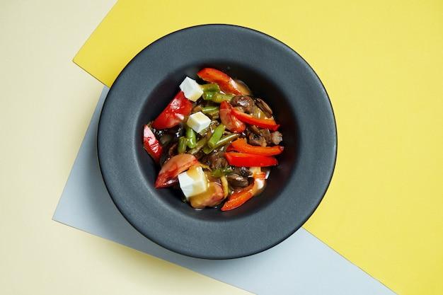 Smakelijke en gezonde vegetarische salade met grillgroenten, dressing en kaas in een zwarte kom op een gekleurd oppervlak. bovenaanzicht op lekker eten