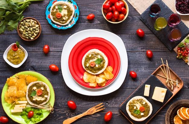 Smakelijke en heerlijke bruschetta met avocado tomaten kaas kruiden chips en sterke drank op een houten achtergrond.