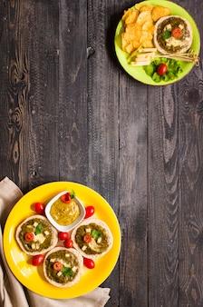 Smakelijke en heerlijke bruschetta met avocado, tomaten, kaas, kruiden, chips en sterke drank, op een houten oppervlak.