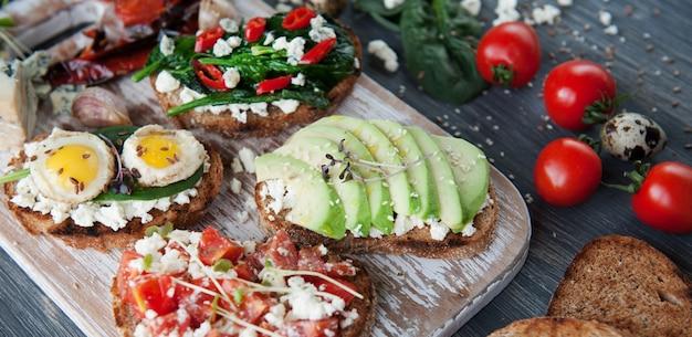 Smakelijke en heerlijke bruschetta met tomaten, spinazie, feta avocado rode chili peper en blauwe kaas.