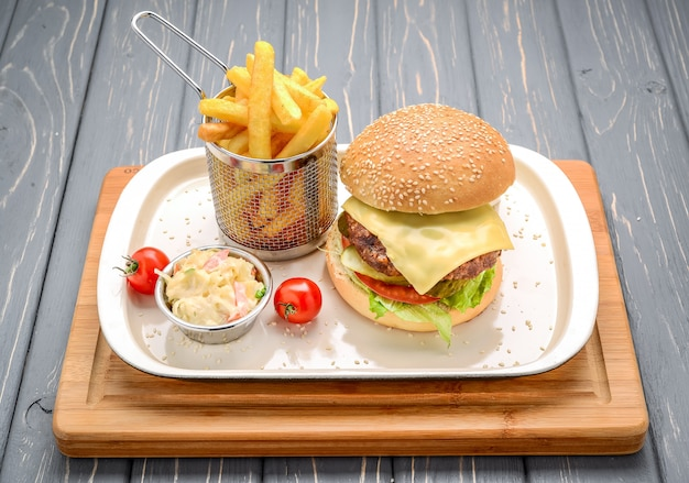 Smakelijke en smakelijke hamburgercheeseburger. op een houten tafel