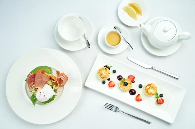 Smakelijke europese ontbijttoost met avocado, rauwe ham en gepocheerd ei en cottage cheese-pannenkoeken of syrniki