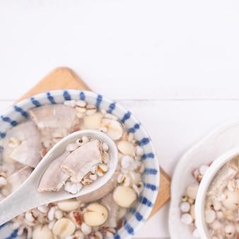 Smakelijke four tonics herb flavour soup, taiwanese traditionele gerechten met kruiden, varkensdarmen op witte houten tafel, close-up, plat lag, bovenaanzicht.