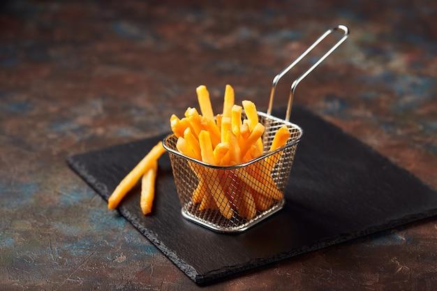 Smakelijke frietjes in ijzeren mand op leisteen snijplank