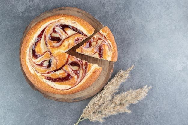 Smakelijke fruitcake met tarwe op een houten bord