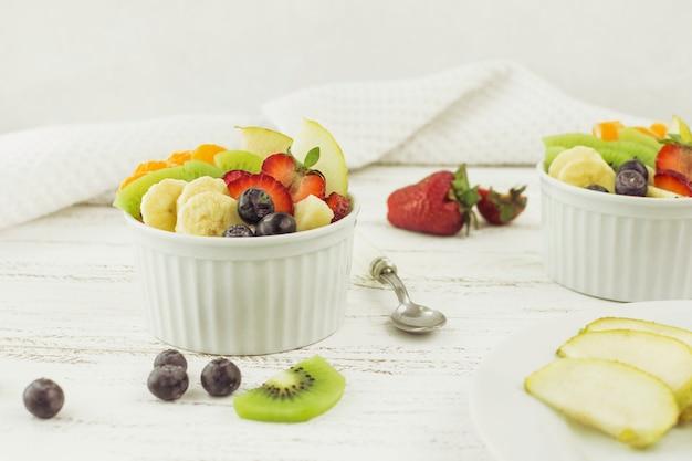 Smakelijke fruitsalades omringd door fruit