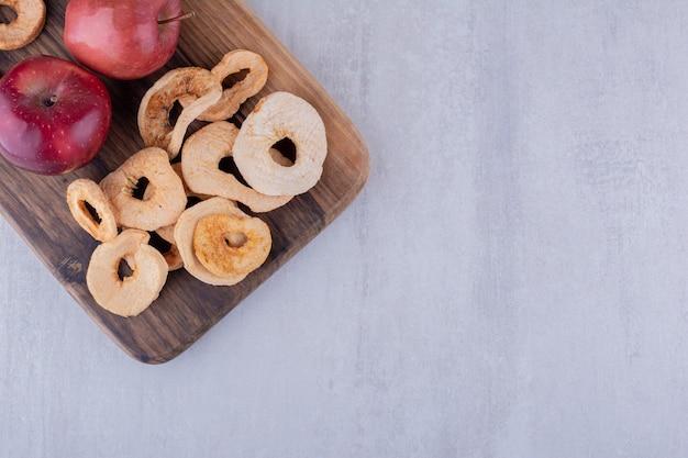 Smakelijke gedroogde appelschijfjes en hele appels op een houten bord op witte achtergrond.