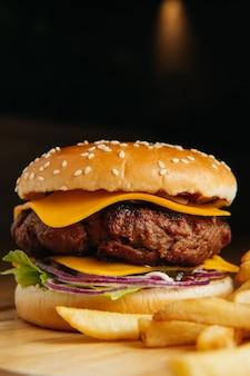 Smakelijke gegrilde grote cheeseburger met frietjes op een houten bord. detailopname. premium foto