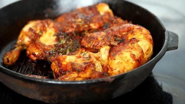 Smakelijke gegrilde kip in een gietijzeren pan