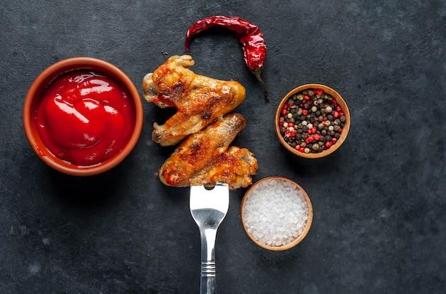 Smakelijke gegrilde kippenvleugel met kruiden op een vork