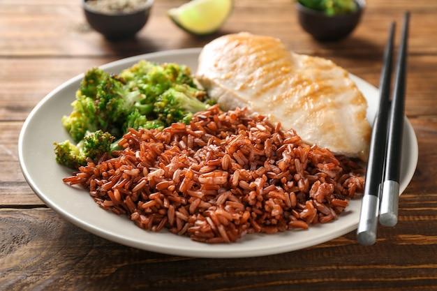 Smakelijke gekookte rode rijst met vlees en broccoli op plaat