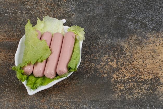 Smakelijke gekookte worstjes en sla op bladvormige plaat.