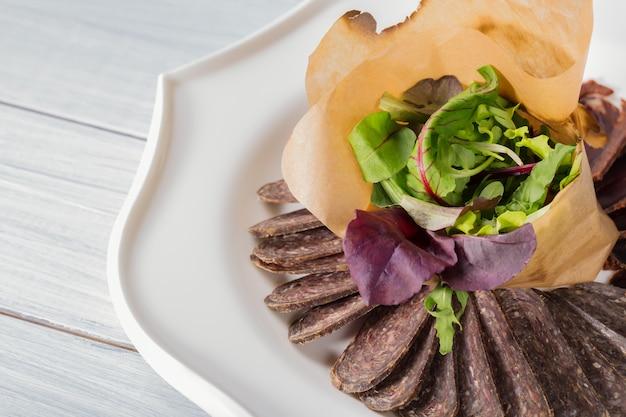 Smakelijke gesneden vleesstukken en salade op plaat en witte houten lijst