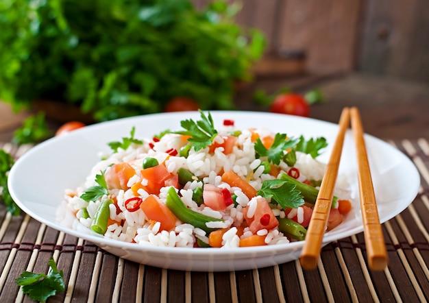 Smakelijke gezonde rijst met groenten in witte plaat op een houten tafel.