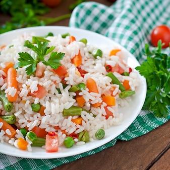 Smakelijke gezonde rijst met groenten in witte plaat op een houten tafel