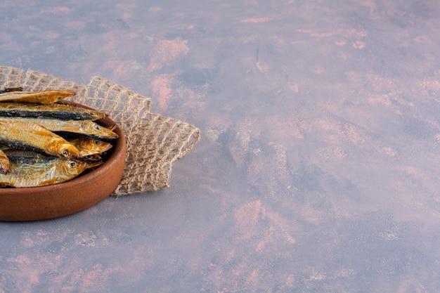Smakelijke gezouten vis op een houten plaat op het marmeren oppervlak