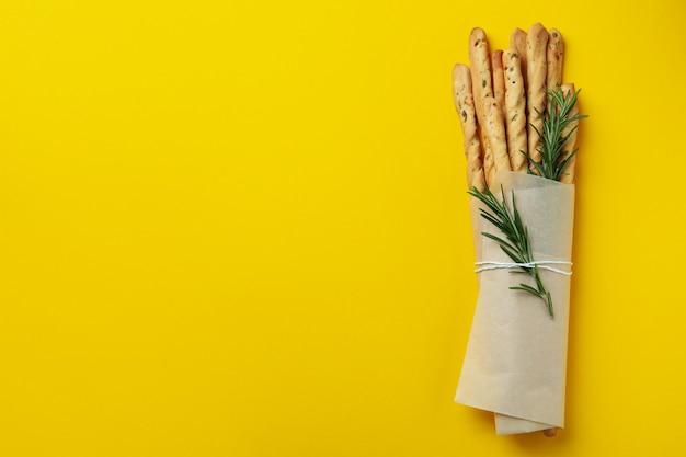 Smakelijke grissini met rozemarijn op gele achtergrond