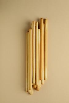 Smakelijke grissini soepstengels op beige achtergrond, bovenaanzicht