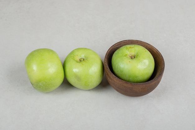 Smakelijke groene appels in houten kom
