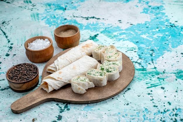 Smakelijke groentebroodjes geheel en in plakjes gesneden met greens en kruiden op helderblauw bureau