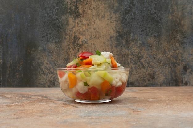 Smakelijke groenten op glasplaat op marmer.
