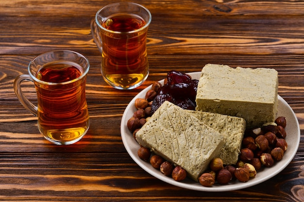 Smakelijke halva met thee, noten, gedroogd fruit op houten tafel