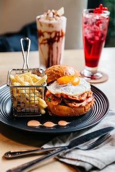 Smakelijke hamburger met gebakken ei geserveerd met frietjes in zwarte plaat op houten tafel.