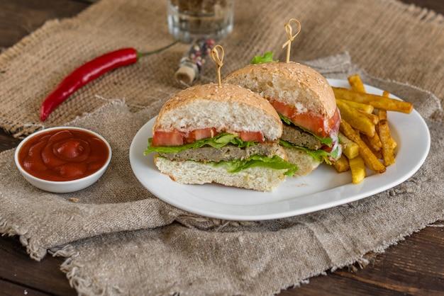Smakelijke hamburger met vlees en groenten tegen een donkere achtergrond. fast food. het kan als achtergrond worden gebruikt
