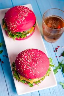 Smakelijke hamburger met, worst, sla en mayonaise geserveerd op een witte plaat