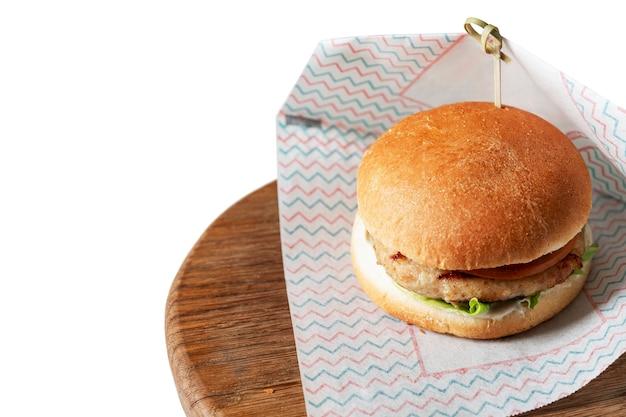 Smakelijke hamburger op een houten bord. ongezond en lekker junkfood. geïsoleerd op een witte achtergrond. ruimte voor tekst.