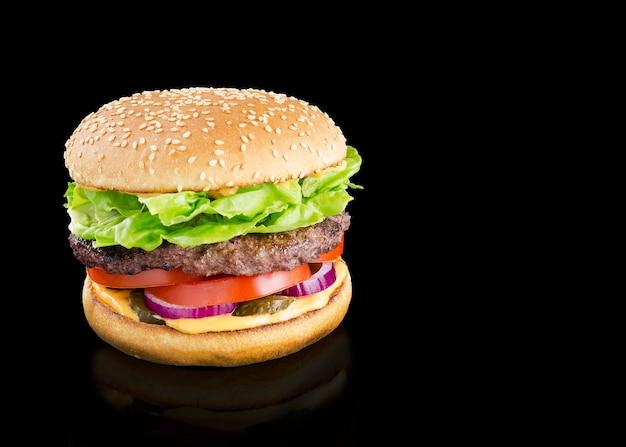 Smakelijke hamburger op een zwarte achtergrond