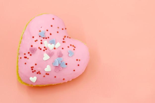Smakelijke hartvormige donut met topping op roze achtergrond.