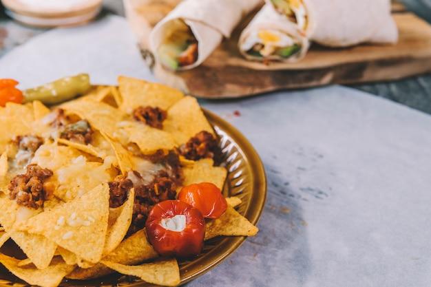 Smakelijke heerlijke mexicaanse gele nachosspaanders in bruine plaat