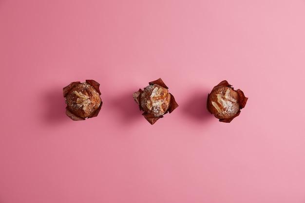 Smakelijke heerlijke muffins gepoederd met suiker en smakelijke vulling van binnen verpakt in bruin papier, klaar voor consumptie. zoetwaren voor uw ochtendontbijt. zelfgemaakte drie cupcakes
