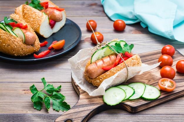 Smakelijke hotdog gemaakt van gefrituurde worst, broodjes en verse groenten, verpakt in perkamentpapier op een snijplank op een houten tafel
