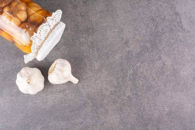 Smakelijke ingelegde knoflook in glazen pot op stenen tafel.