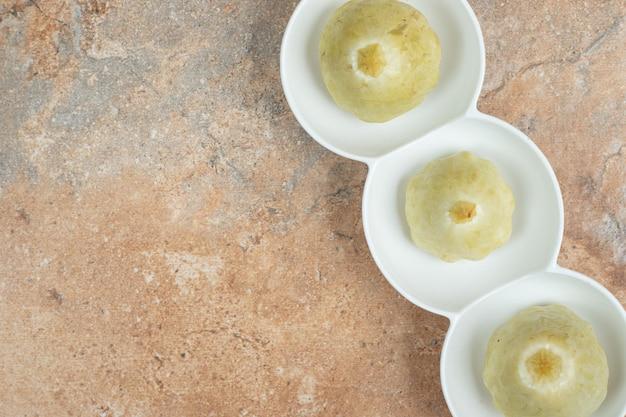 Smakelijke ingelegde vruchten op witte platen