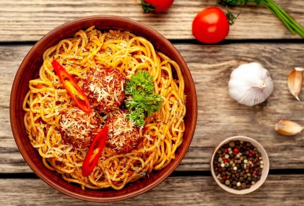 Smakelijke italiaanse pasta spaghetti met gehaktballen, parmezaanse kaas op een bord, snijplank op een houten achtergrond. uitzicht van boven