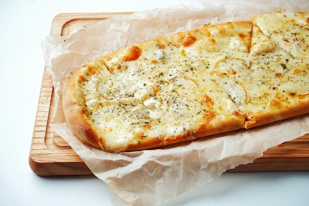 Smakelijke italiaanse pizza 4 kaas met peer op een houten dienblad op een grijze tafel. bovenaanzicht. italiaanse keuken