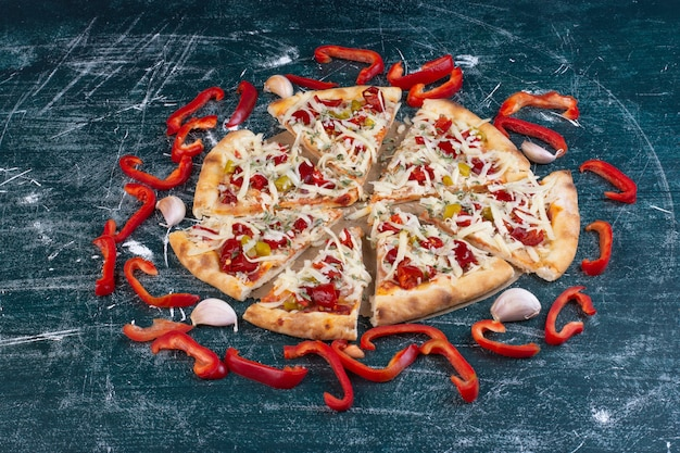 Smakelijke kaasachtige pizza op blauw met verse groenten.