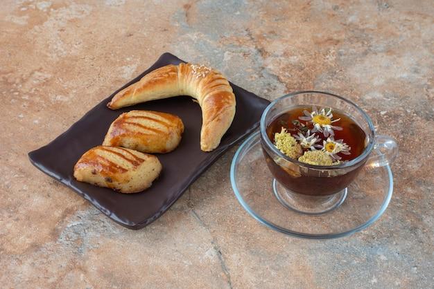 Smakelijke kamille thee met koekjes op marmer