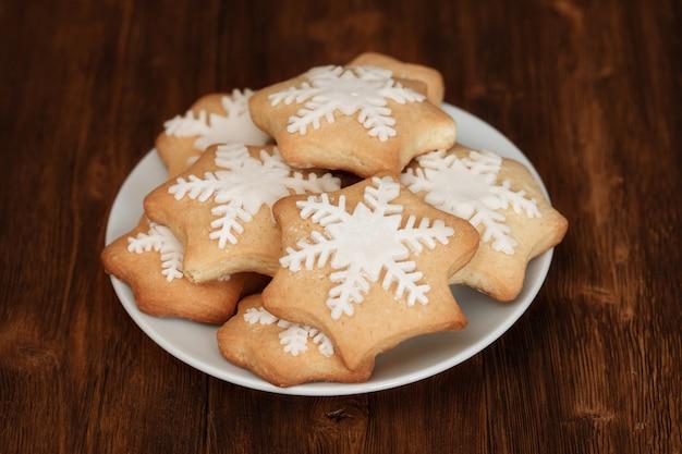 Smakelijke kerstmis coockies versierd met suiker op plaat, close-up