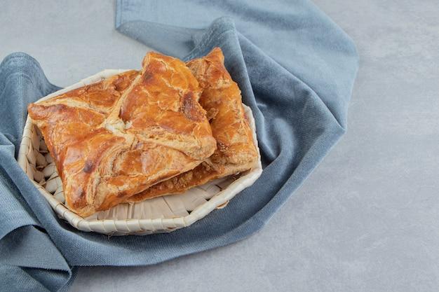 Smakelijke khachapuri gebakjes in houten mand.