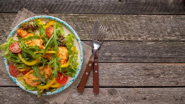 Smakelijke kipsalade op een bord geserveerd vork en mes. geroosterde kippen verse groenten en sla. bovenaanzicht