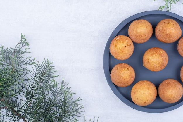 Smakelijke kleine cakes op plaat met dennentak