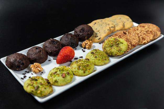 Smakelijke kleurrijke chocoladekoekjes op de zwarte achtergrond