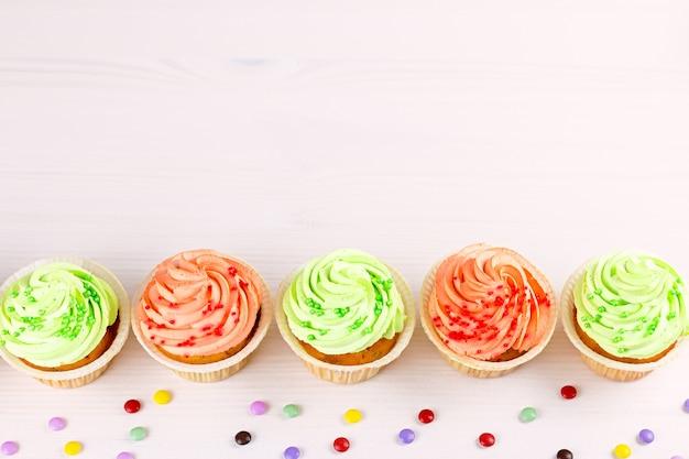 Smakelijke kleurrijke cupcakesclose-up op bokehachtergrond met exemplaarruimte. verjaardagsfeest snoep