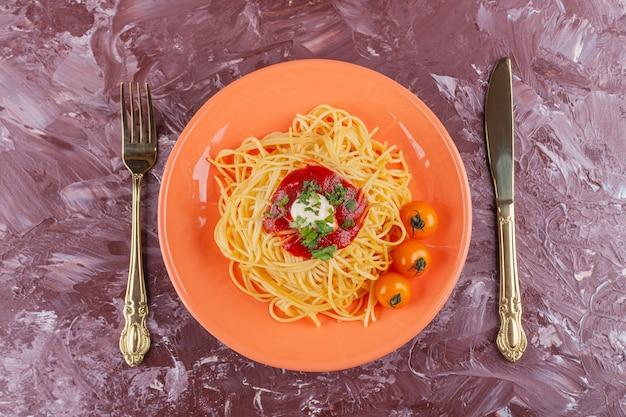Smakelijke kleurrijke smakelijke gekookte spaghetti met tomatensaus en verse gele kerstomaatjes.