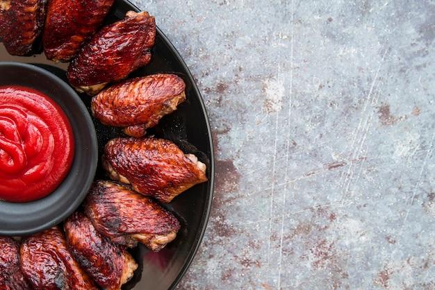 Smakelijke knapperige kippenvleugels met saus in kom over concrete vloer