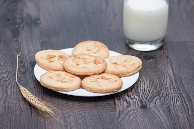Smakelijke koekjeskoekjes met amandel en tarwe op de plaat op houten achtergrond met glas